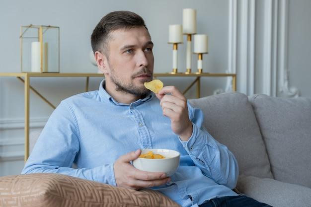 Человек сидит на диване и ест картофельные чипсы Premium Фотографии