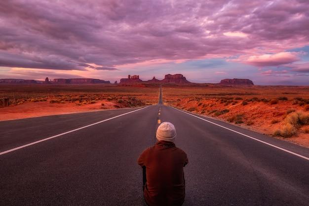 남자는 길에 앉아 미국 애리조나 주 모뉴먼트 밸리 근처의 핑크, 골드 및 마젠타 색상으로 놀라운 일출을 존경합니다.