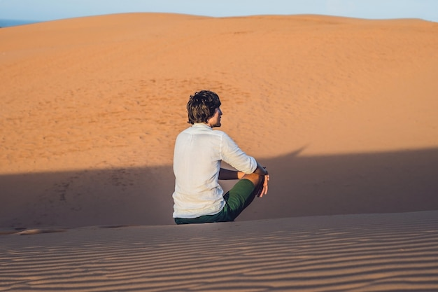 A man sits on the sand in the desert.