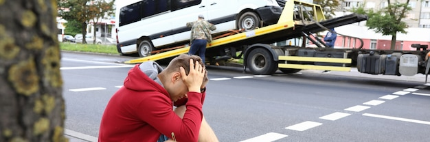 Man sits on side of road holding his head with his hands next to wrecked car after car accident. traffic violation concept