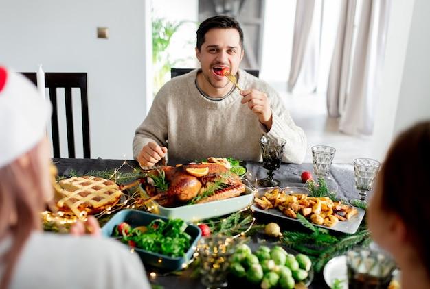 Man sits at a table at christmas dinner