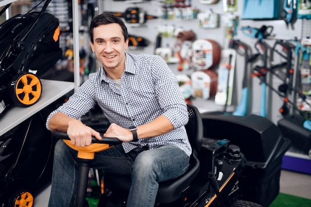 A man sits behind the wheel of a lawnmower and smiles.