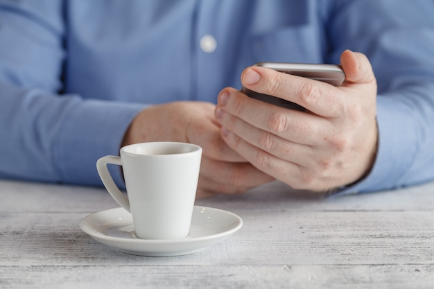 Man sits with smartphone at table with cup of coffee