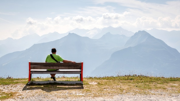 A man sits on a wooden bench at the top of the alps and looks at the beautiful mountain landscape.