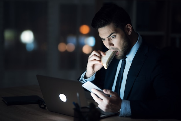 A man sits at work, eats and looks at the phone.