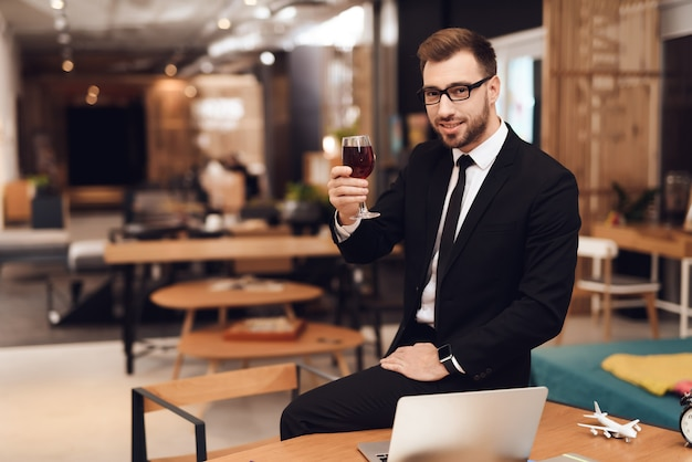 A man sits at work with wine and looks at the camera.