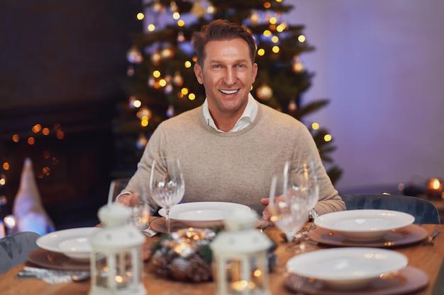 クリスマスのテーブルのそばに一人で座っている男。高品質の写真
