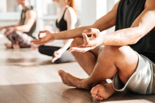 Человек сидит и медитирует в позе лотоса с группой