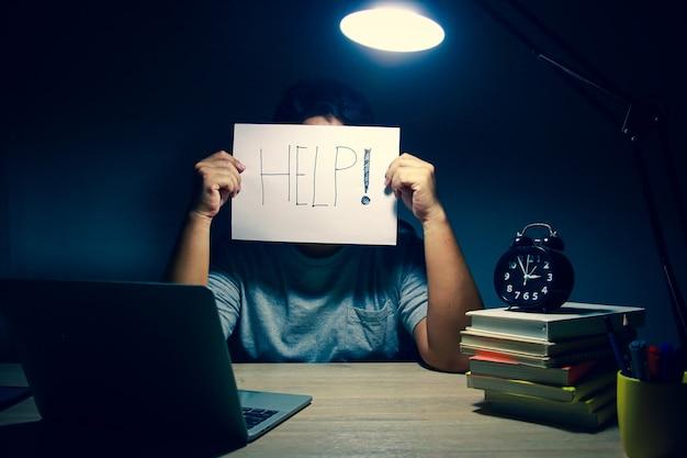 夜遅くに家に座って仕事をしている男性。在宅勤務のコンセプト、社会的距離。