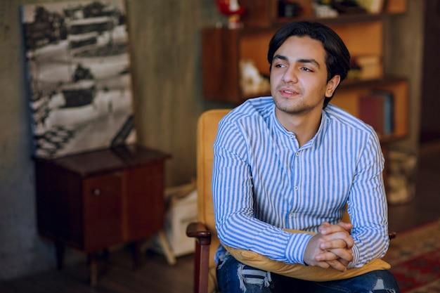 Uomo seduto sulla poltrona in un coffeeshop e sognare. foto di alta qualità