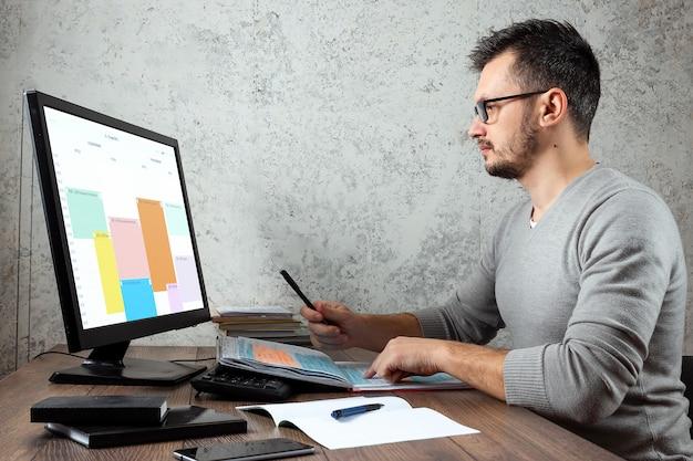コンピューターに取り組んでいる、事務所のテーブルに座っている男の人。