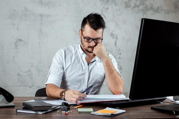 男は、重要な論文に取り組んでいる、オフィスのテーブルに座っています。