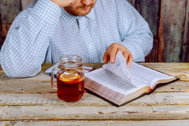 聖書を読んでテーブルに座っている男の人