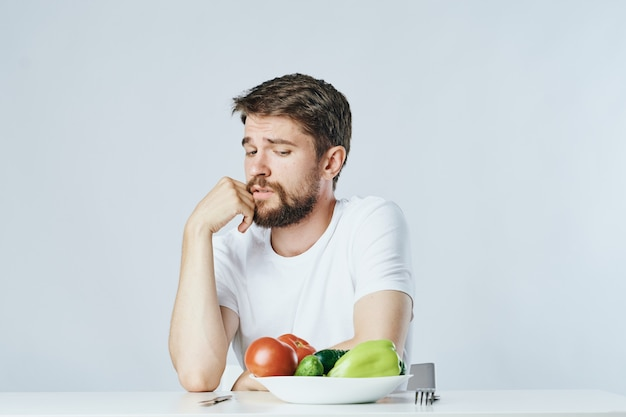Человек сидит за столом с овощами