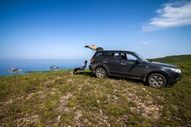 Человек сидит в тени черной машины на вершине холма на морском побережье