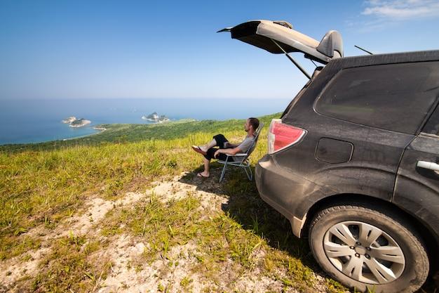 Человек сидит в тени черного внедорожника на вершине холма на морском побережье
