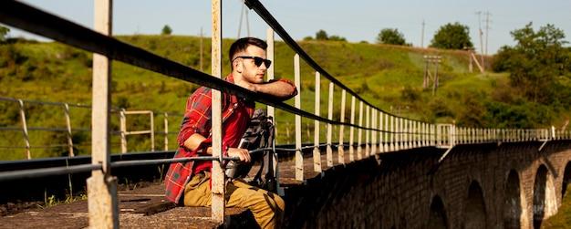 橋の端に座っている男