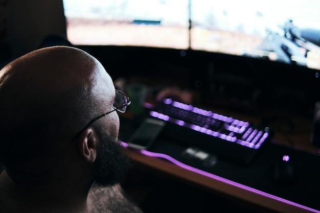 Человек сидит за своим компьютером, играя в компьютерные игры