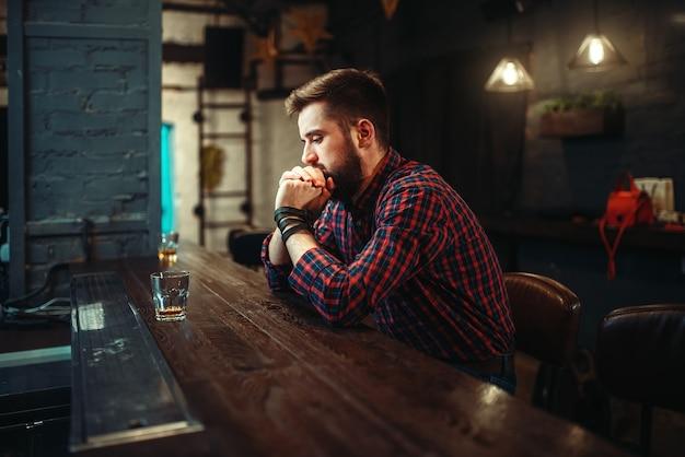 Человек сидит за барной стойкой и пьет алкоголь
