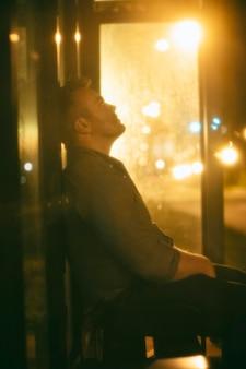 市内の夜にバス停に座っている男