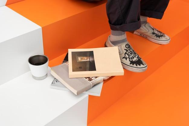 책과 커피 컵 옆에 있는 다방에 앉아 있는 남자