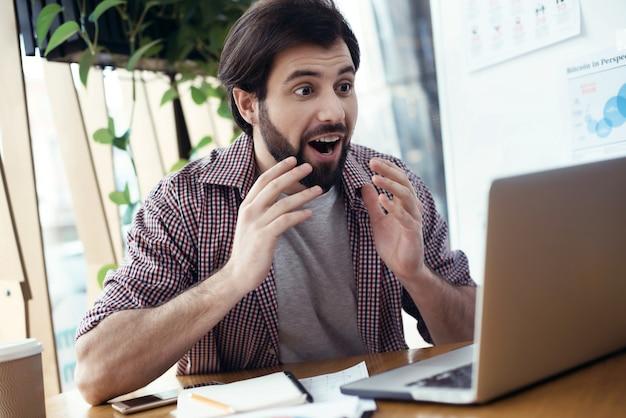 Человек, сидящий за столом в творческом стильном офисе, глядя на л