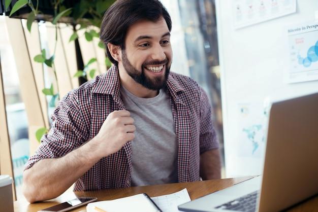Человек, сидящий за столом в творческом стильном офисе, глядя на s