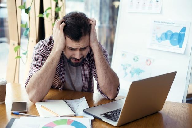 Человек, сидящий за столом в творческом стильном офисе, стрессовом wo