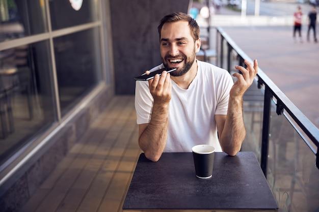 스마트 폰 및 커피와 함께 테이블에 앉아 남자