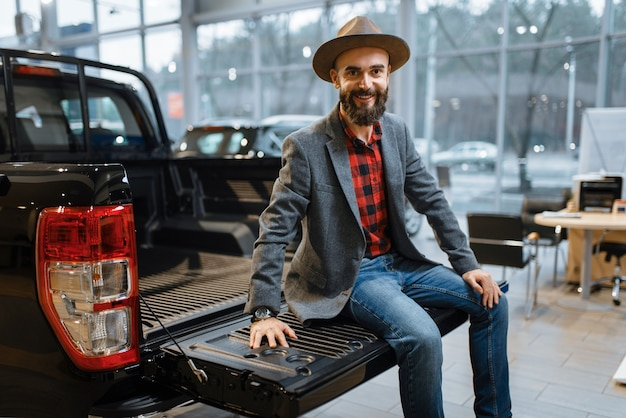 Man sitting in the back of new pickup truck in car dealership. customer in vehicle showroom, male person buying transport, auto dealer business