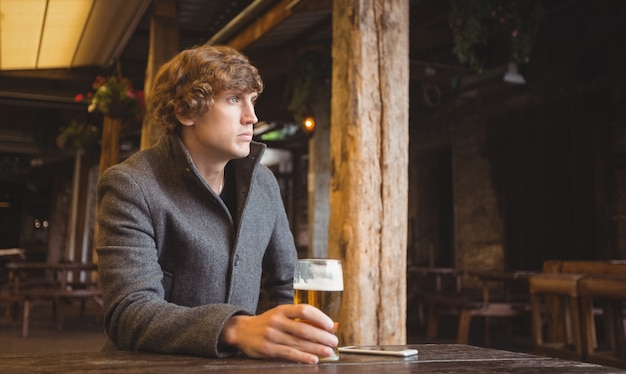 Man sitting in bar with glass of beer on table