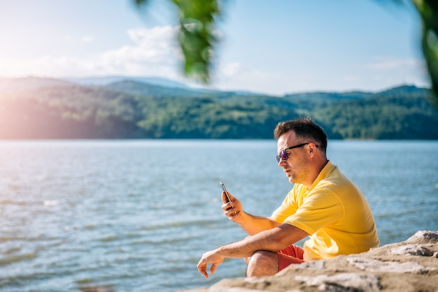 Man sitting on a beach and using smart phone