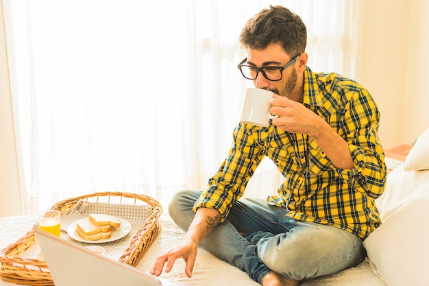 Man sitting on bed drinking the coffee with breakfast and laptop on bed