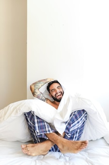 Man sitting on bed laughing