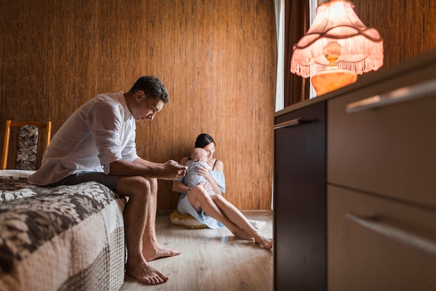 Man sitting on bed using mobile phone with his wife carrying her baby