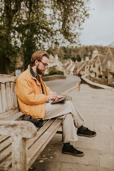 Man sitting on a bench and working on tablet in the village