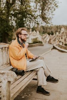 Uomo seduto su una panchina e lavorando su tablet nel villaggio