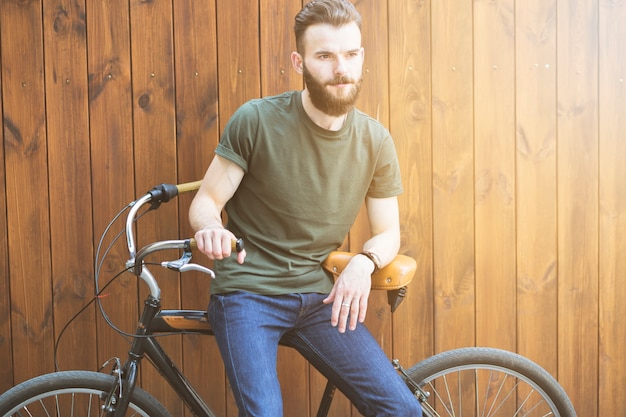 Man sitting on bicycle against wooden backdrop