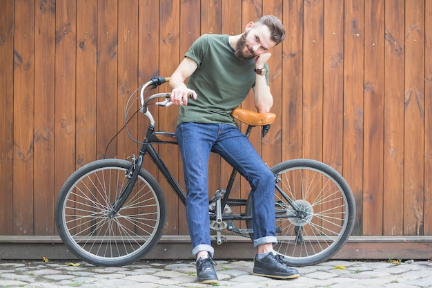 Man sitting on bicycle against wooden wall