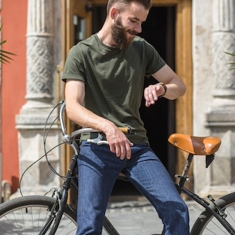 Man sitting on bicycle looking at time on wrist watch