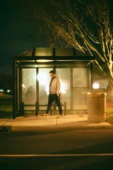 Uomo seduto alla stazione degli autobus di notte in città