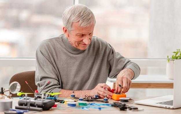 クワッドコプターの修理プロセス中にさまざまなカラフルなプロのツールでテーブルのそばに座っている男