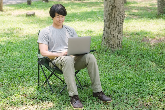 Man sitting on camping chair and working with laptop computer in the garden
