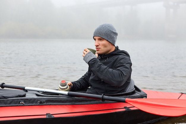 Man sitting in canoe, resting after active paddling on kayak, drinking coffee from thermos, looking at beautiful nature, wearing black jacket and cap, sitting in middle of lake