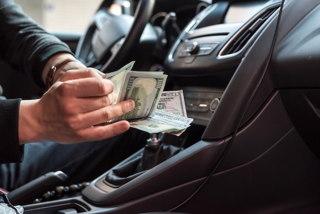 Man sitting in a car counting dollar banknotes as bribes