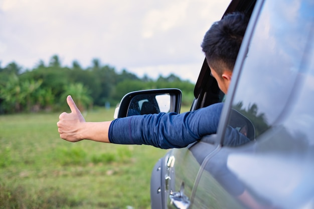 Man sitting in car happily reach out hand with thumb up.