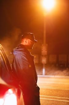 Man sitting next to car at night