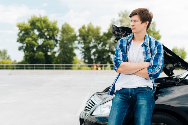 Man sitting on car with copy space