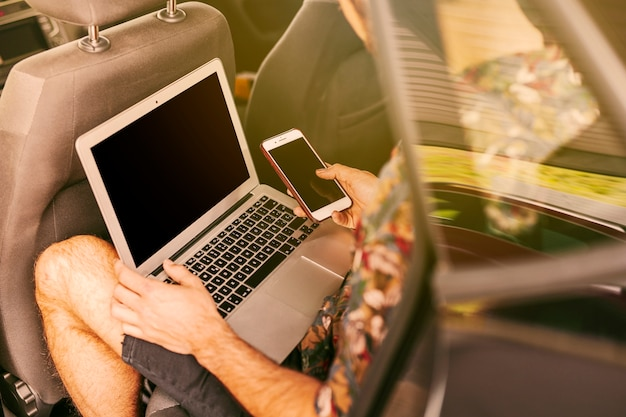 Man sitting in car with laptop and smartphone