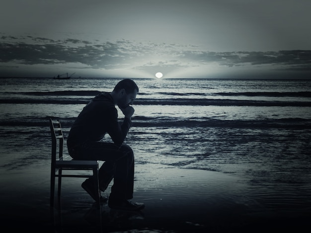 Man sitting on the chair on the coast at night